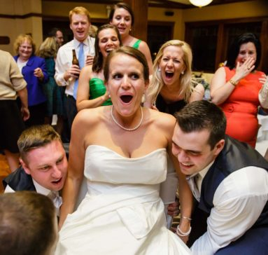 Wedding guests lifting bride up on a chair