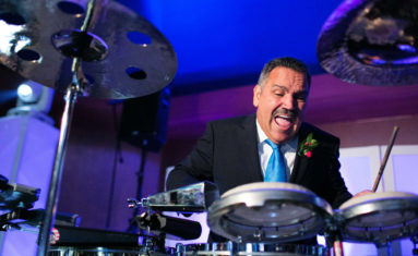 Father of the bride plays the drum at the wedding reception